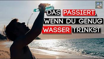 Mann steht am Strand und trinkt Wasser